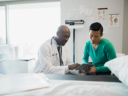 A doctor and patient reviewing the patient's medical case in an exam room.