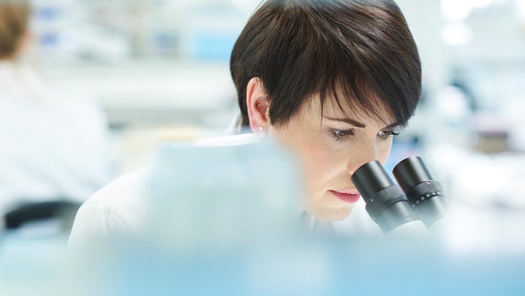 Female scientist in her lab looking into a microscope with another scientist in the background.