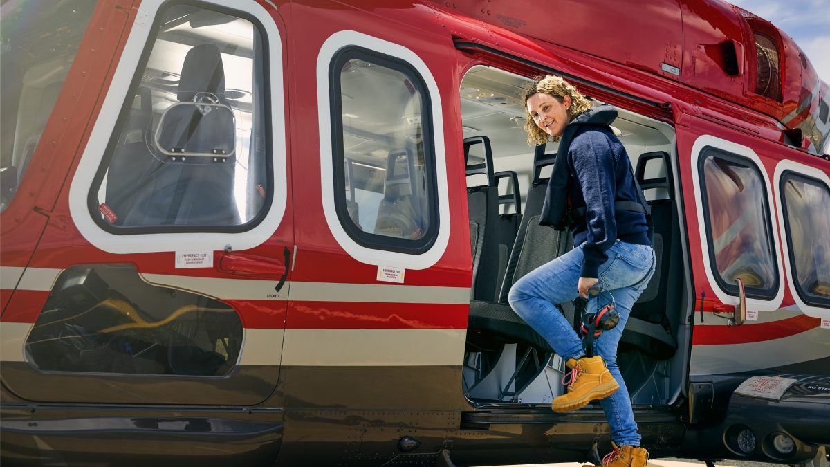 woman stepping in to helicopter