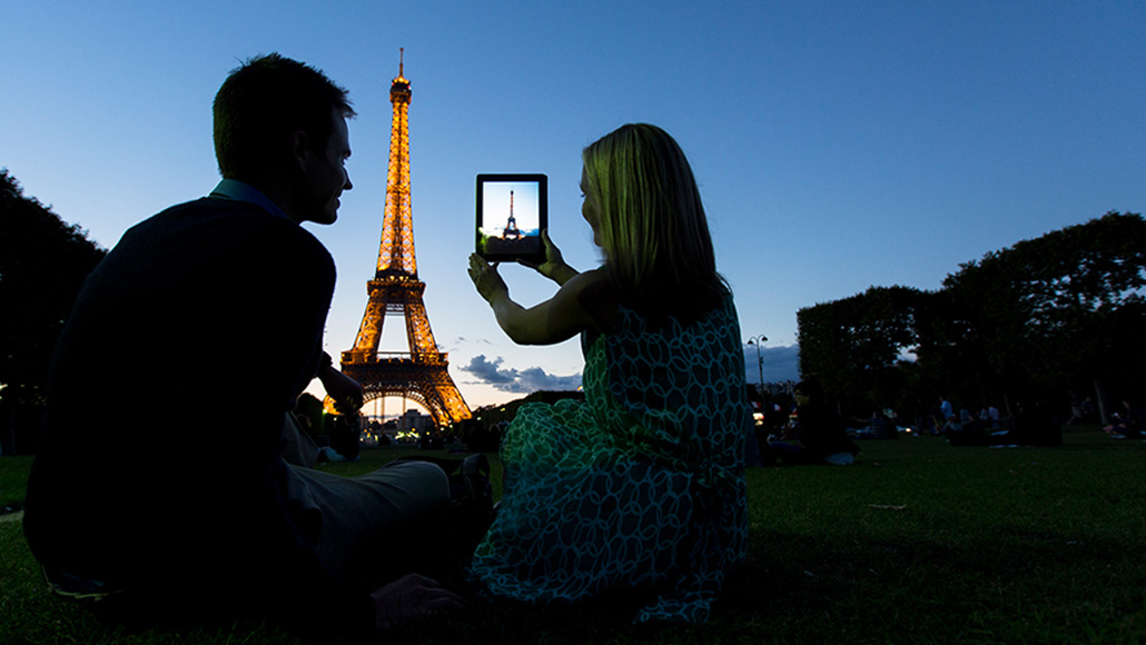 man and woman taking picture of Eiffel tower at night