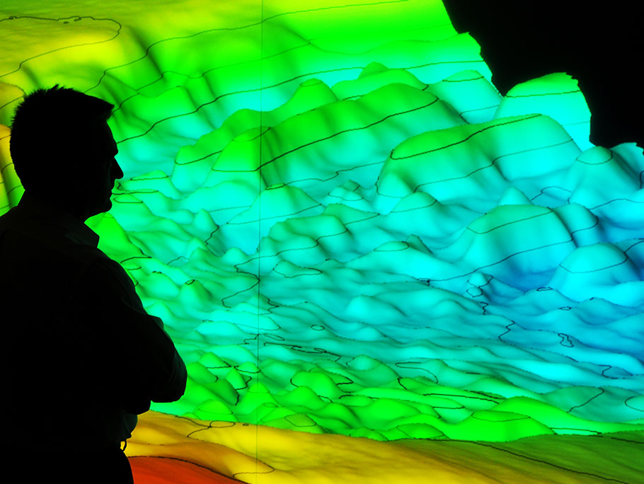 man standing in front of 3D seismic technology visualization