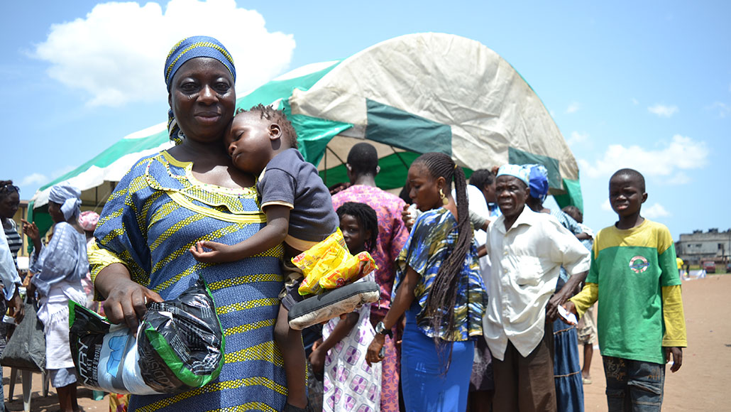 Nigerian woman holding child in front of crowd.