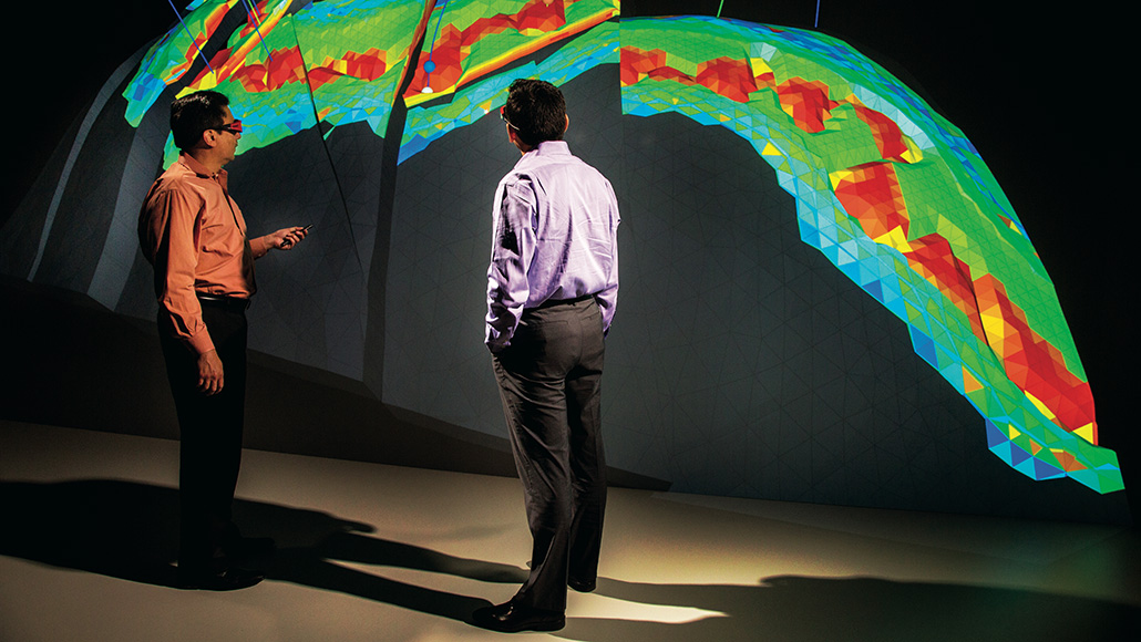 two men stand in front of seismic imaging readout