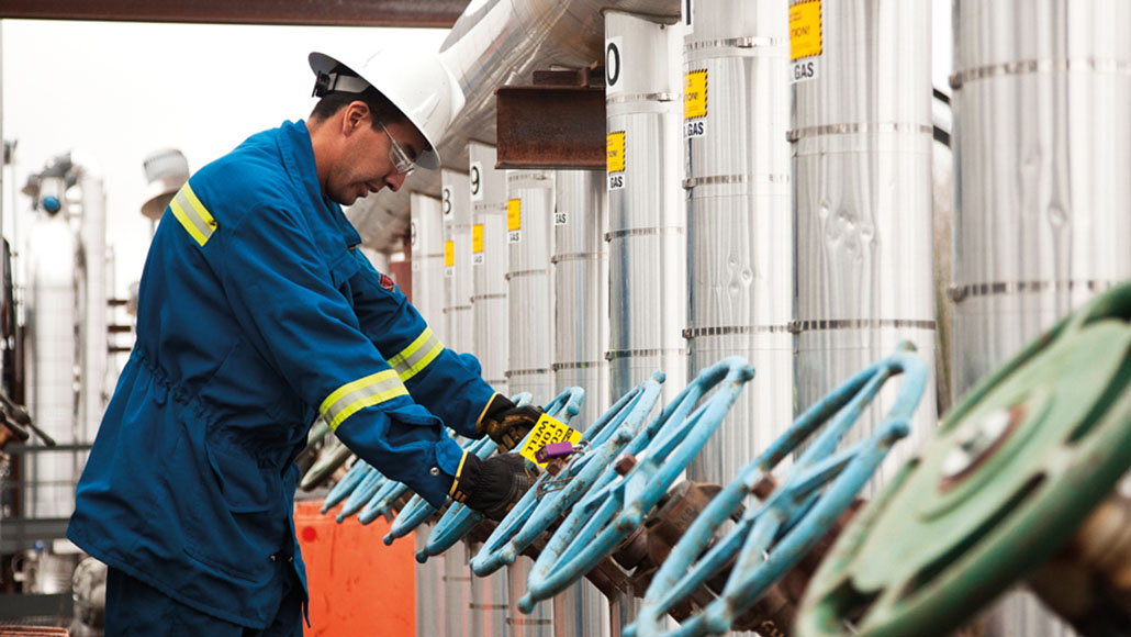 An ExxonMobil employee turning a gas valve