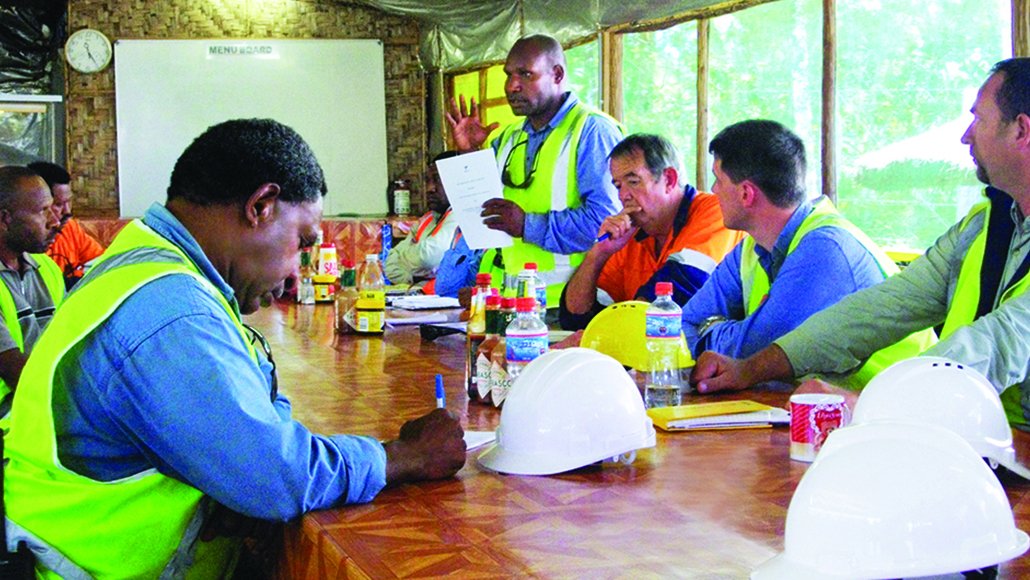 Workers in neon vests gathered around a table for a meeting