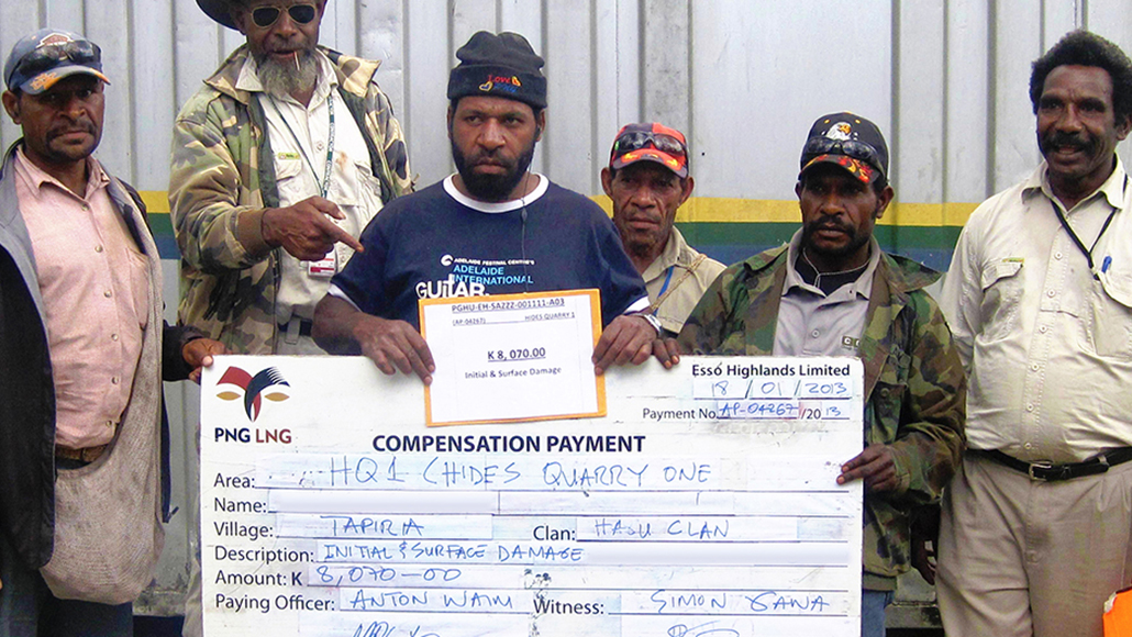 Local community members with a compensation payment check