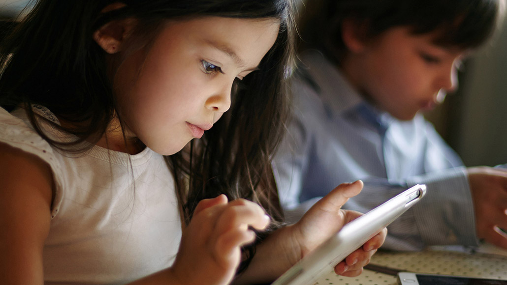 Young boy and girl reading on tablet devices.